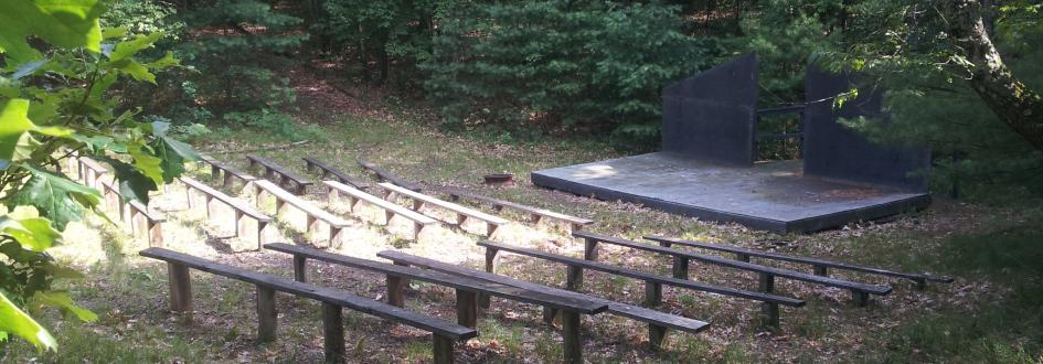 Rows of benches sit in front of a small wooden platform with a black backdrop.