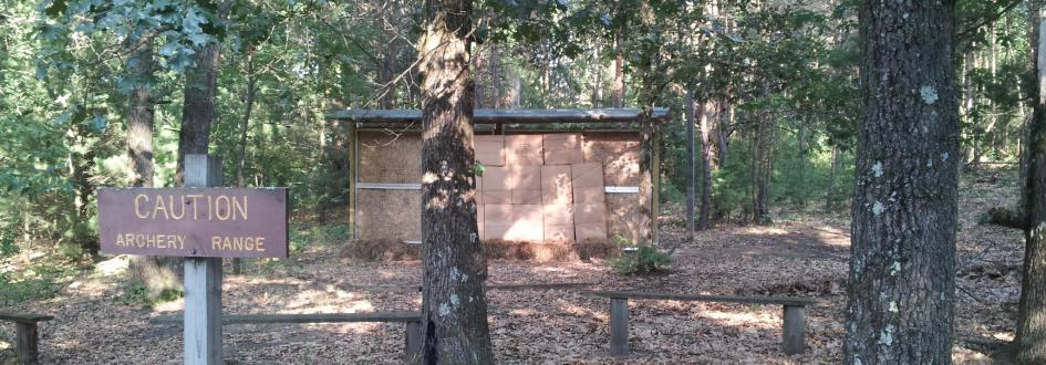 """A sign that says """"Caution: Archery Range"""" sits in front of two benches and a small wooden wall."""