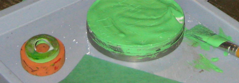 Green and orange cylindrical pieces rest next to a paintbrush with green paint.