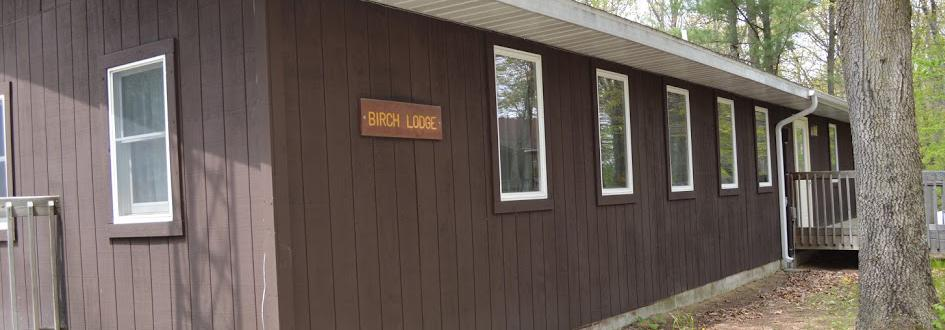 """A brown rectangular building featuring a sign that says """"Birch Lodge."""""""