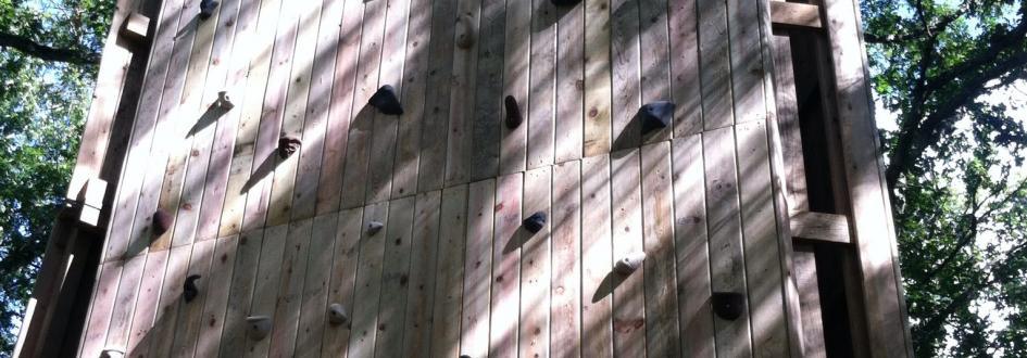 A large wooden climbing tower featuring several footholds.