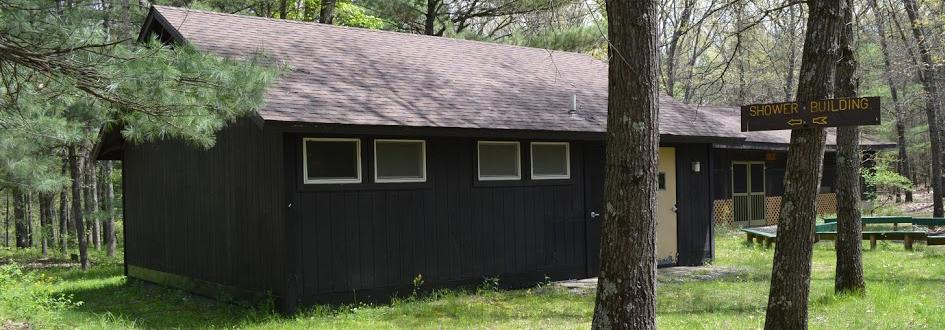 A brown shower building in the foreground and screened-in Jack Pine Pavilion in the background, surrounded by trees.