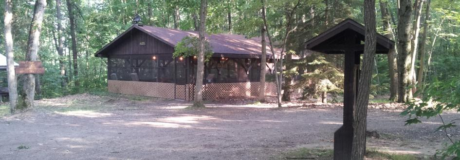 Screened-in Red Pine Pavilion exterior, surrounded by trees and a dirt path.