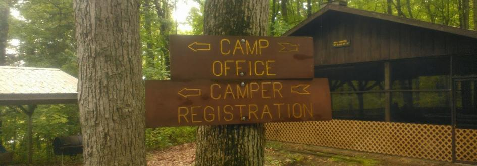"Signs that say ""Camp Office"" and ""Camper Registration"" pointing to the left."