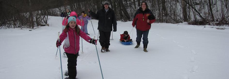 Two adults walk as several children snowshoe through the woods. One adult pulls a child in a sled.