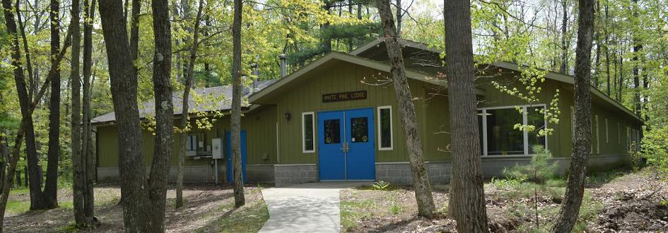 White Pine Lodge exterior in summer. The green building has bright blue doors.